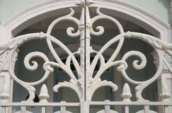 Un bianco ha dipinto il portone del ferro battuto con progettazione intrecciante delle viti Fotografie Stock