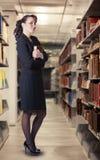 Un bibliotecario atractivo que se coloca en las pilas Fotografía de archivo