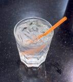 Un bicchiere d'acqua con ghiaccio e paglia arancio sulla tavola di pietra nera Fotografia Stock