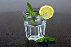 Un bicchiere d'acqua con il limone e la menta fra le gocce di acqua Bevanda di rinfresco di estate Fotografia Stock