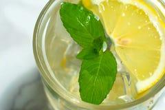 Un bicchiere d'acqua con il limone e menta e ghiaccio Bevanda di raffreddamento immagini stock