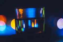 Un bicchiere d'acqua e le luci della città uguagliante fotografie stock libere da diritti
