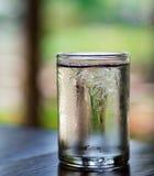 Un bicchiere d'acqua sulla tavola di legno Fotografia Stock Libera da Diritti