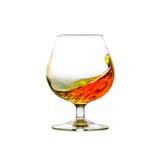 Un bicchiere da brandy riempito del cognac con liquido commovente Immagine Stock Libera da Diritti