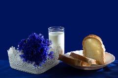 Un bicchiere di latte con pane e fiordalisi Fotografia Stock