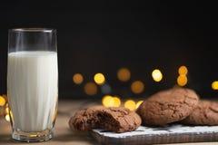 Un bicchiere di latte e biscotti del cioccolato, con le bei luci e concetto, spazio della copia fotografie stock libere da diritti