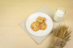 Un bicchiere di latte, tre pezzi di biscotti di pepita di cioccolato in un piatto rotondo bianco e mazzo secco del grano immagini stock