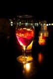 Un bicchiere di vino con il cocktail ed il ghiaccio rossi Immagine Stock