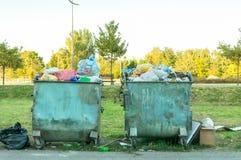 Un bidone della spazzatura di due metalli in pieno di immondizia che inquina la via della città Fotografia Stock