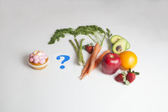 Un bigné contro Frutta e verdure con un punto interrogativo Fotografie Stock