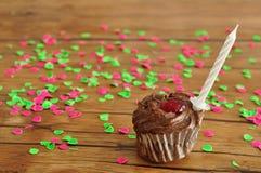 Un bigné del cioccolato con una candela di compleanno Immagine Stock