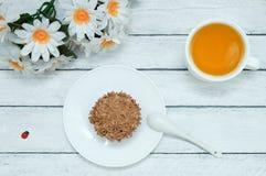 Un bigné su un piatto bianco, una tazza di tè verde, un mazzo di fiori della margherita fotografia stock libera da diritti