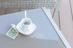 Un billet d'un dollar américain et tasse de café vide sur une table en verre de café extérieur Paiement, astuce image stock