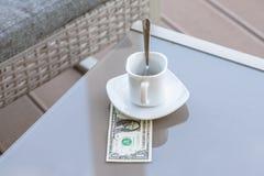 Un billet d'un dollar américain et tasse de café vide sur une table en verre de café extérieur Paiement, astuce photo stock