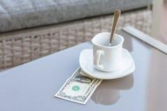 Un billet d'un dollar américain et tasse de café vide sur une table en verre de café extérieur Paiement, astuce images libres de droits