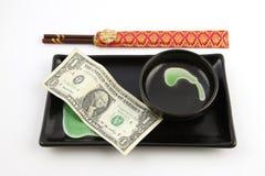 Un billet d'un dollar d'Etats-Unis d'une plaque de sushi Photographie stock libre de droits