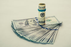 Un billet d'un dollar 100 enroulé qui se repose sur des autres a pêché le billet d'un dollar 100 d'isolement sur le fond blanc Photo stock