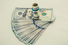 Un billet d'un dollar 100 enroulé qui se repose sur des autres a pêché le billet d'un dollar 100 d'isolement sur le fond blanc Image libre de droits