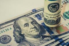 Un billet d'un dollar 100 enroulé qui se repose sur des autres a pêché le billet d'un dollar 100 d'isolement sur le fond blanc Photo libre de droits