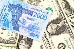 Un billet de banque d'Afrique occidentale de franc avec un fond des Etats-Unis billets d'un dollar un photographie stock libre de droits