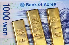 Un billet de banque 1000 gagné sud-coréen avec trois barres d'or étroitement  photos stock