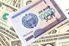 Un billete de banco del som de Uzbekistán con los billetes de dólar de Estados Unidos uno imágenes de archivo libres de regalías