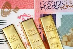 Un billete de banco sudanés de cincuenta libras con tres barras de oro fotos de archivo libres de regalías