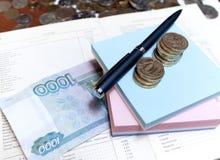 Un billete de banco y monedas Fotos de archivo