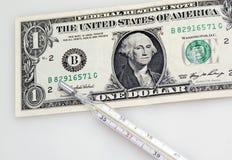 Un billete de banco y termómetro del dólar Imagen de archivo libre de regalías