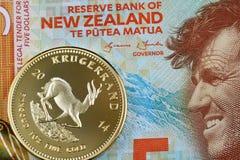 Un billete de dólar de cinco Nueva Zelanda con una moneda surafricana de Krugerrand del oro foto de archivo libre de regalías
