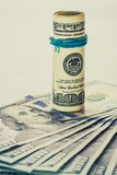 Un billete de dólar en espiral 100 que se basa sobre otro pescó el billete de dólar con caña 100 aislado en el fondo blanco Fotografía de archivo libre de regalías