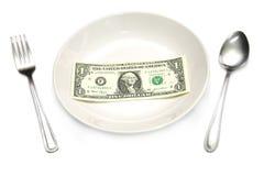 Un billete de dólar en placa Foto de archivo