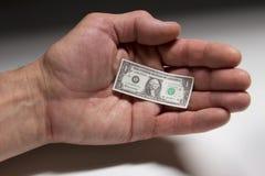 Un billete de dólar minúsculo dentro de la palma del hombre Foto de archivo libre de regalías