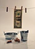 Un billete de dólar que cae en el fondo blanco Imagenes de archivo