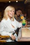 Un biondo nel bianco ad un contatore della barra con un cocktail Immagini Stock