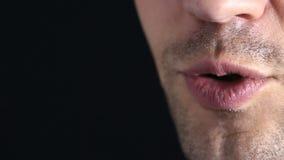 Un bisbiglio della persona nella macchina fotografica Primo piano delle labbra bisbiglio su un fondo nero archivi video