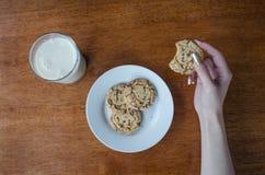 Un biscotto nella mano delle donne ed in un bicchiere di latte fotografia stock