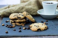 Un biscuit avec du chocolat se trouve sur un conseil en pierre avec une tasse de coff images libres de droits