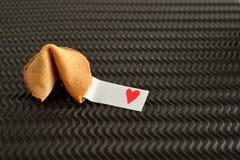 Un biscuit de fortune avec un morceau de papier avec un coeur rouge Images stock