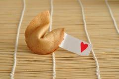 Un biscuit de fortune avec un morceau de papier et d'un coeur rouge Photo libre de droits