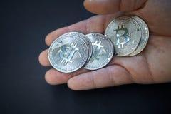 Un Bitcoin argenté est dans la main ouverte La pièce de monnaie brille et réfléchit la lumière Le fond est foncé et abstrait La d image stock