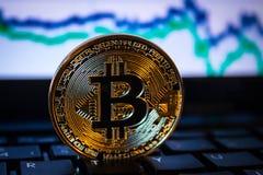Un bitcoin de oro con el fondo del teclado y del gráfico concepto comercial de moneda crypto Foto de archivo