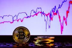 Un bitcoin de oro con el fondo del teclado y del gráfico concepto comercial de moneda crypto Imagenes de archivo