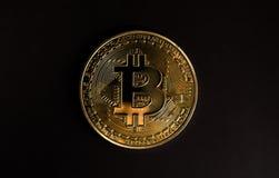 Un bitcoin en backround negro Imágenes de archivo libres de regalías