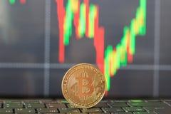 Un bitcoin sulla tastiera e un grafico della crescita e della caduta dei prezzi Fotografia Stock