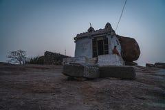Un bizcocho borracho hindú del monje que se sienta en un templo de piedra en la puesta del sol en karnakata del hampi foto de archivo libre de regalías