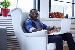 Un blackman che si siede sulla sedia immagine stock libera da diritti