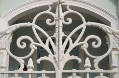Un blanc a peint la porte de fer travaillé avec la conception s'entrelaçante de vignes Photos stock