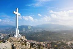 Un blanco cruza encima la ciudad de Jaén en la montaña, un símbolo de la ciudad con las montañas de Sierra Magina en fondo el día fotografía de archivo libre de regalías