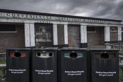 Un bloc abandonné de toilette, se délabrant avec l'âge, avec quatre bacs de recyclage dans le premier plan, aussi en mauvais état Photographie stock